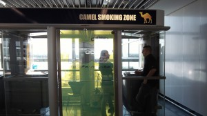 "Smokers in a glass cage at ""Fraport,"" the airport in Frankfurt, Germany."
