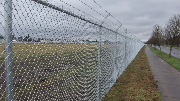 The new fence stretches along Price road on the east side of Albany Airport. Timber Linn Park is to the right.