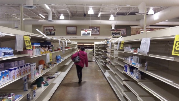 A shopper scans Ray's nearly empty shelves on Tuesday.