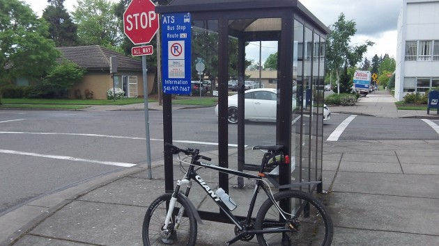 Something else likely to be illegal: Using bus shelter as bike stand.