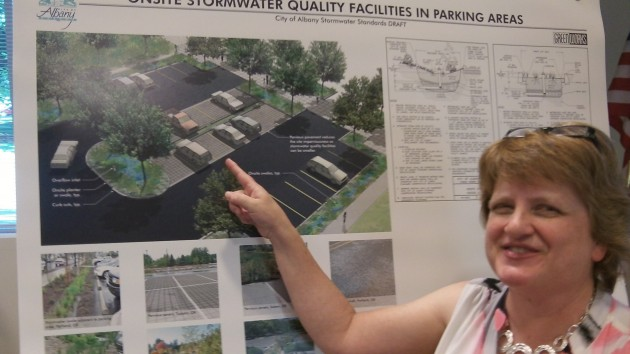 Consultant Lori Faha with an illustration of a stormwater feature in a parking lot.