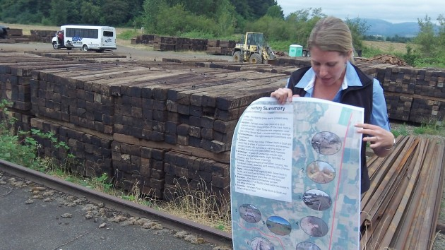 Cody Ross documented features of the rail corridor. Salvaged cross tries are stacked behind her, at Alpine Junction.