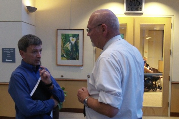 Outside the council meeting, City Attorney Jim Delapoer, right, confers with Mark Stoner of Lowe's.
