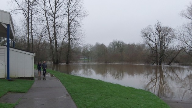 Two people walk past an inundated part of Monteith Riverpark on Dec. 23.