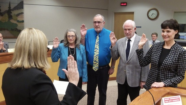 City Clerk Mary dibble swears in re-elected council members, from left, Bessie Johnson, Ray Kopczynski and Dick Olsen and Mayor Konopa.