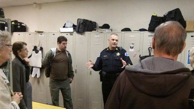 Capt. Jeff Hinrichs shows a tour group the police station locker room Tuesday.