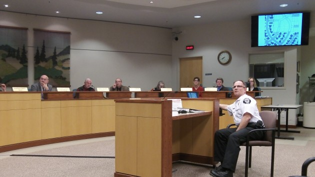 Fire Marshal Mike Trabue and the Albany council study a street map on one screen while the audience can see the other.