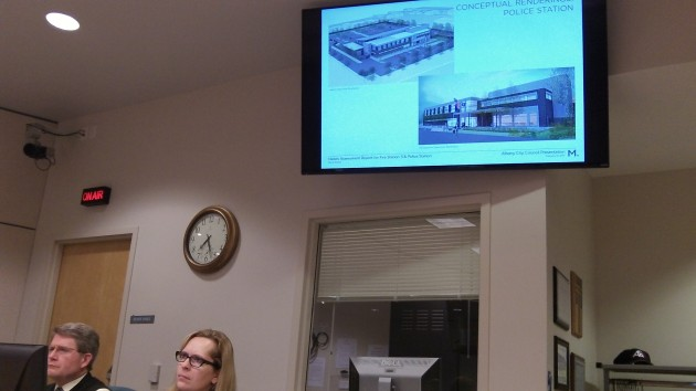 Police station renderings appear on screen above Finance Director Stewart Taylor and City Clerk Mary Dibble.