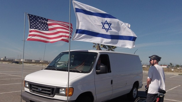 The owner of a van parked near a California beach makes a point with two flags last week.