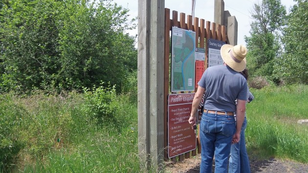 Visitors study the map of the Luckiamute Natural Area at the paddlers' access parking lot.