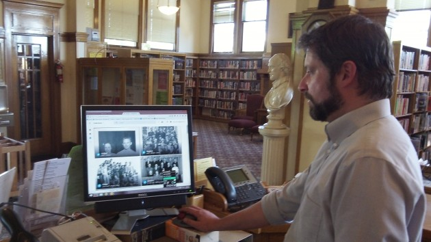Librarian Jason Darling with a screen of images made by Bob Potts.