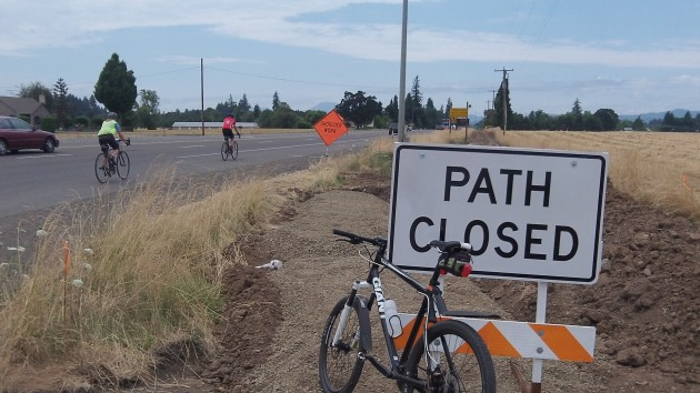 Two cyclists head west on 34 from Riverside Drive, where a separate  bikeway is being built.