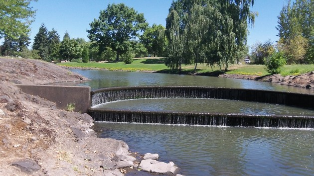 Water trickles over the structure that creates the pond in Periwinkle Park.