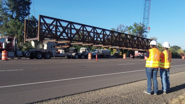 Two ODOT employees watch as the bridge is lifted onto s truck and trailer Monday.
