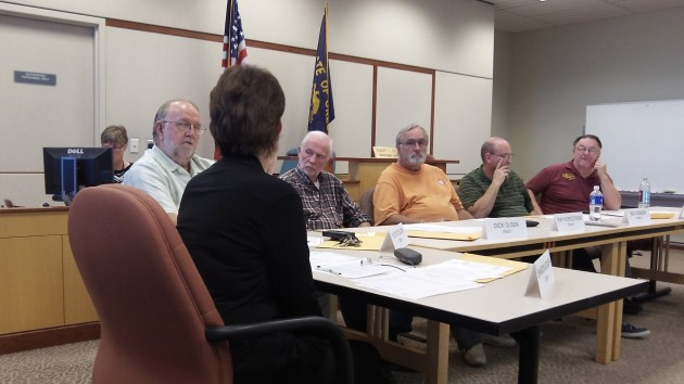 Councilor Floyd Collins, left, talks to Mayor Sharon Konopa as other councilors listen Monday.