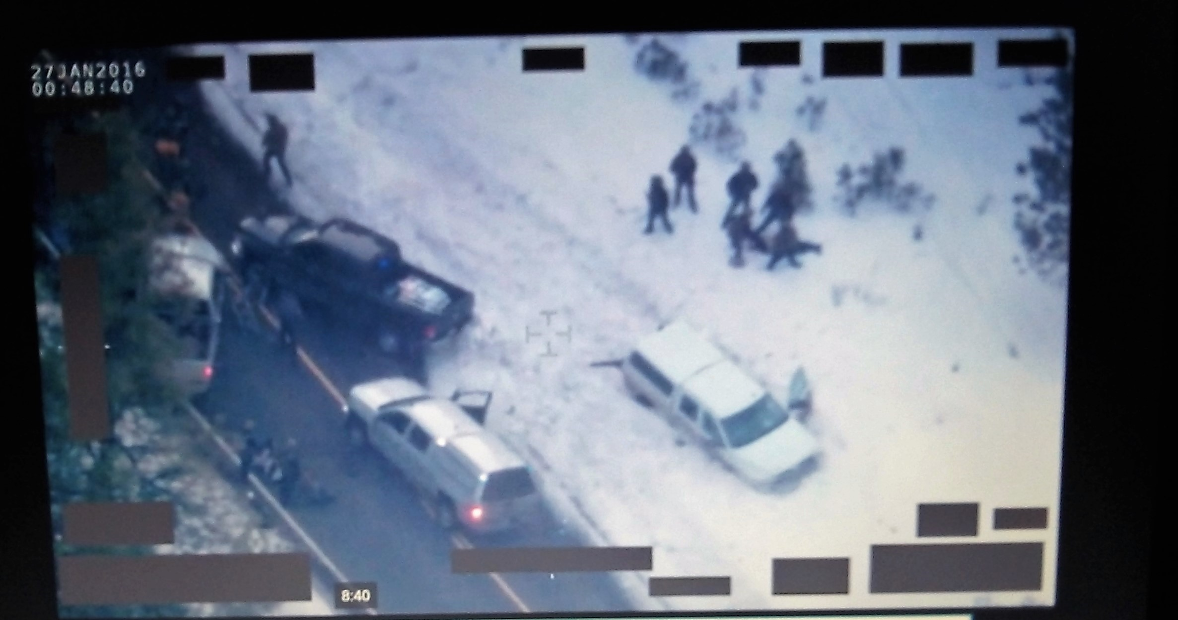 FBI video: Law officers gather around the body of the dead rancher after others in the truck have come out.