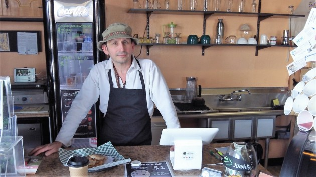 Alex Contreras behind the counter of his coffee shop.