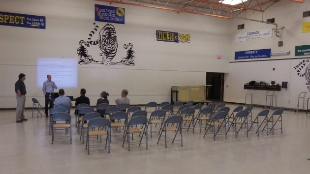 Jim Stouder, left and Josh Wheeler chat with four people who showed up for a community meeting in the gym at North Albany Middle School Thursday night.