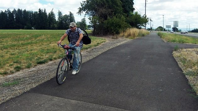 A traveler on the bike path alongside Highway 34.