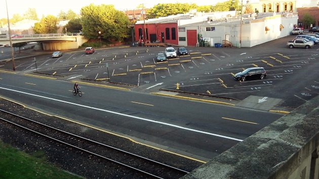 "A cyclist passes the ""east anchor"" site on Water Avenue Tuesday evening."