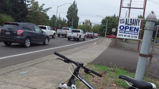 Traffic waits for a green light at the Santiam-Pacific junction, next to campaign sign put up by two council members.