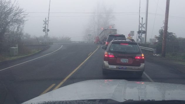 In the fog Friday morning, a ruck waits - and waits -- to turn left from Independence Highway.