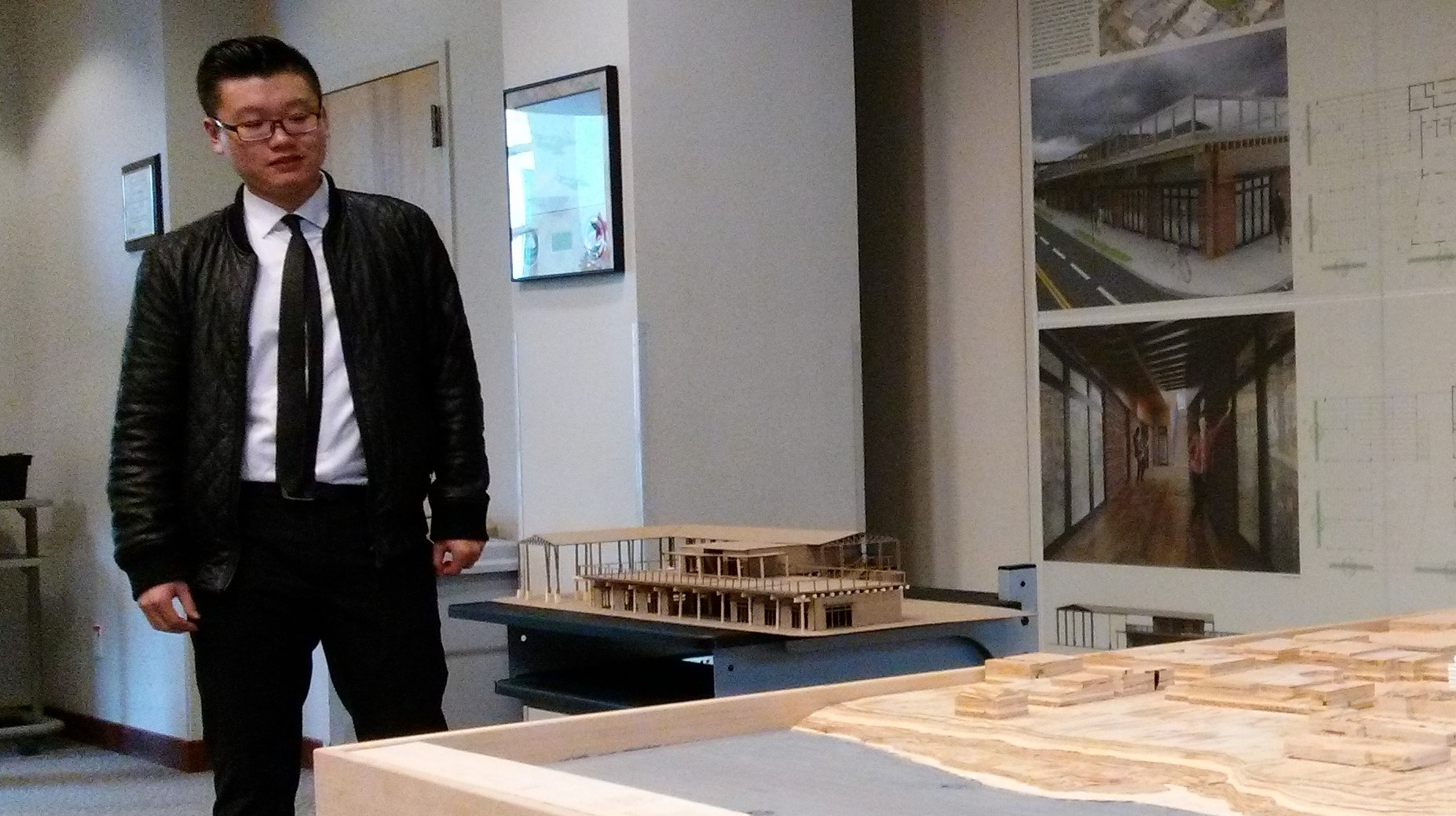 Steven Liang with a model of his idea for a market buiding facing Water Avenue.