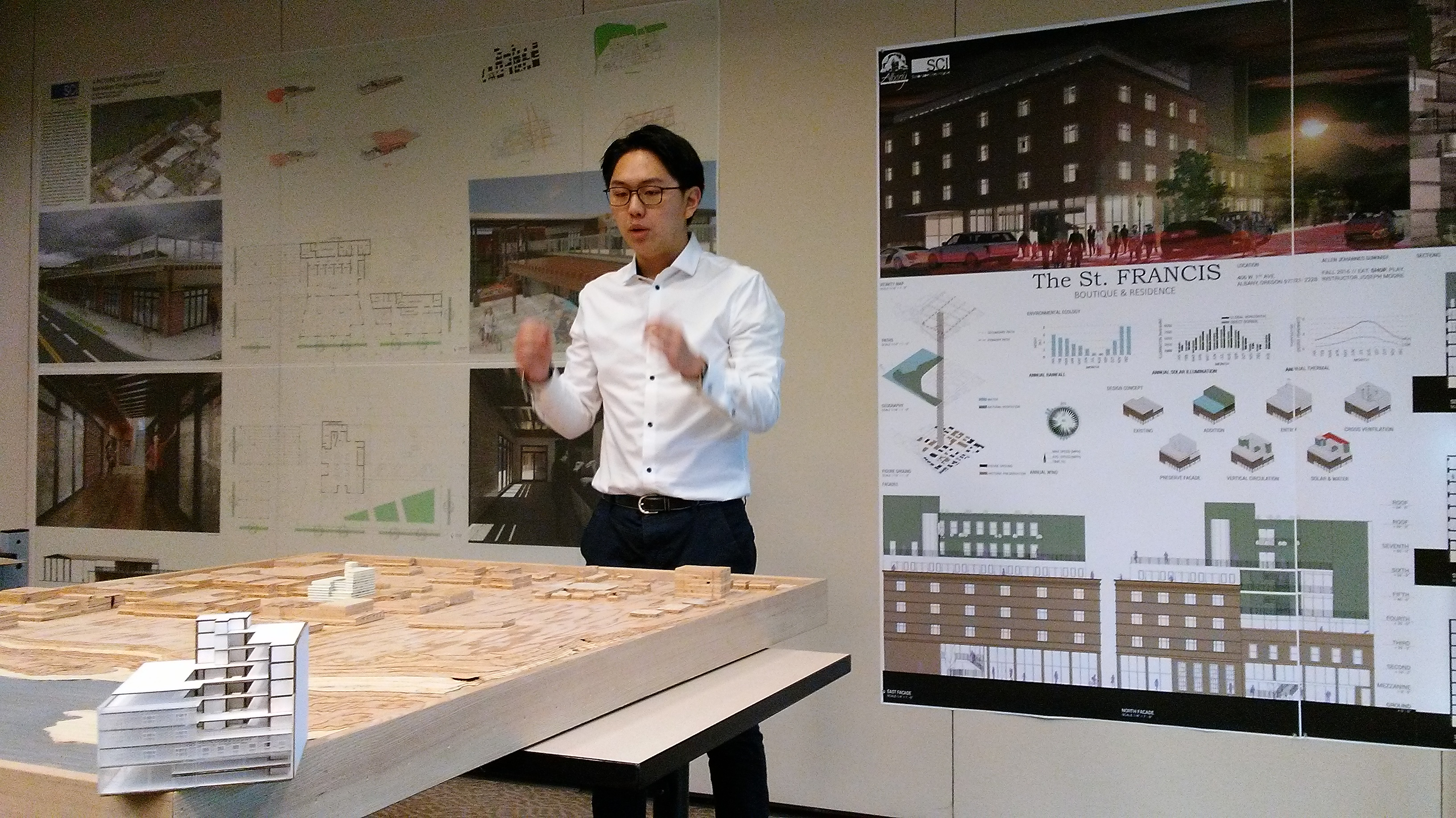 Allen Suwardi's St. Francis design in drawings and two models, one on its site in a plywood mockup of donwtown, the other in the foreground..