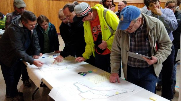 Studying the map of potential bikeway routing alternatives.
